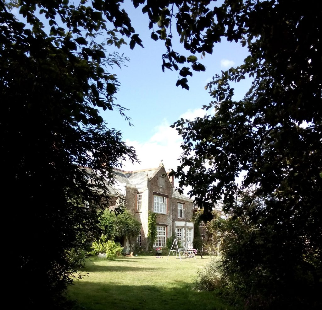photo of Beech Hill House in Mid Devon through some silhouetted tree branches on a sunny summer day